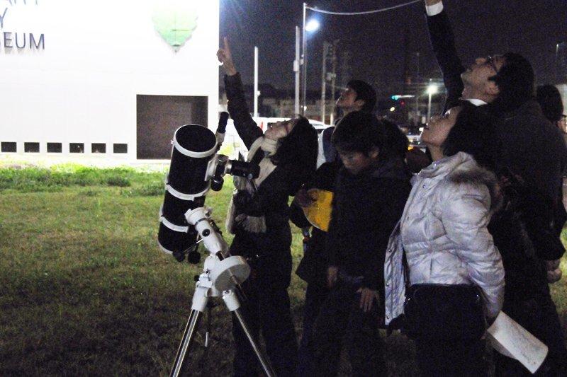 レーザーポインターで星の位置を示す羽村さんと空を見上げる参加者の方々